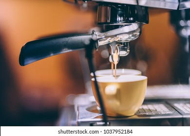 Details of espresso machine pouring and brewing fresh, creamy coffee in local bistro, restaurant or pub