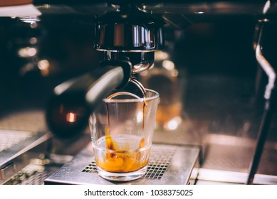 Details of espresso machine pouring and brewing fresh, creamy coffee in local bistro, restaurant or bistro