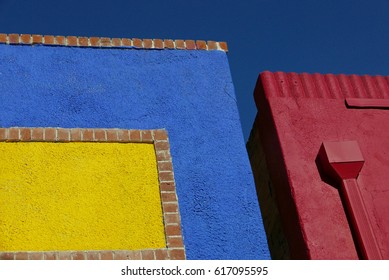 Details of facades of brightly blue, yellow and red painted building, looking up at the blue sky