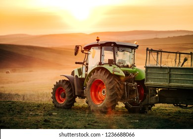Details of farmer working in the fields with tractor on a sunset background. Agriculture industry details