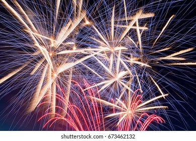 Details of fireworks, red, blue, orange, yellow and white with sky in the background