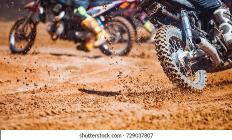 Details of flying debris during an acceleration with mountain bikes race in dirt track in sunshine day time in blurry background. Concept of focus between an accelerate in action sport