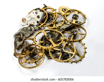The details (gears, springs, pendulums) of the clockwork in a pile on a white background. Selective focus.
