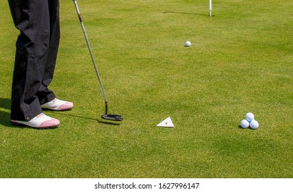 Details of the golf players on the golf site, sunny day, fresh green grass and no face.