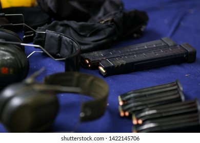 Details with gun clips and 9mm ammunition on a table on a shooting range