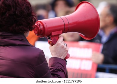 Details with the hand of a woman holding a megaphone during a peaceful protest
