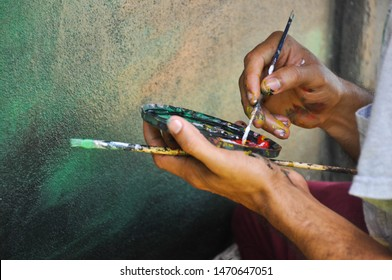 Details of the hands of a paintor working with cans of diferents colors, the brush on his fingers  dirty with paint while doing a mural art work artist painting