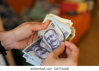 Details with the hands of a young lady counting banknotes of 50 and 100 Romanian Lei currency