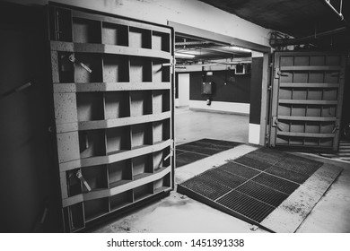 Details with the heavy metal doors of a nuclear explosion shelter (fallout shelter), four stories below ground in a deep underground parking place - black and white.