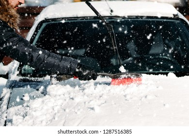 Details of human hand cleaning snow off car during winter snowfall