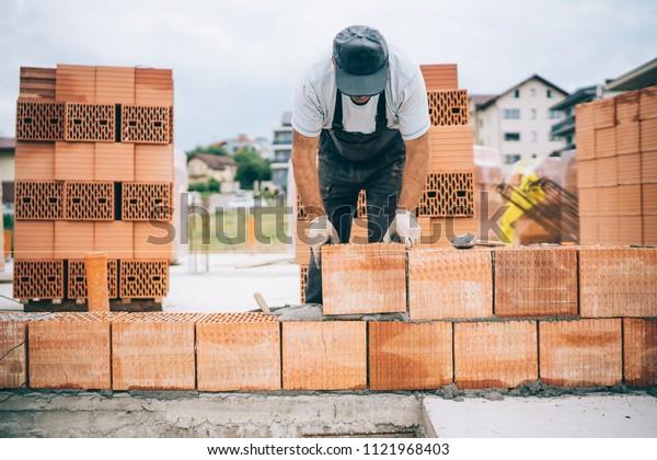 details of industrial bricklayer installing bricks on construction building site