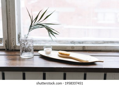 Details of interior, aromatic candle in glass and wooden brush with natural bristles on metal tray on wooden window sill