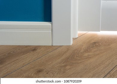 Details in the interior. Laminated parquet floors immitating oak texture, white baseboard, white door