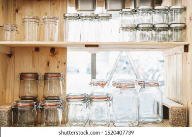 Details of interior zero waste shop. Wooden shelves with different reusable glass jars for buying and storage products. Sustainable food shopping in plastic free grocery store. Local small business.