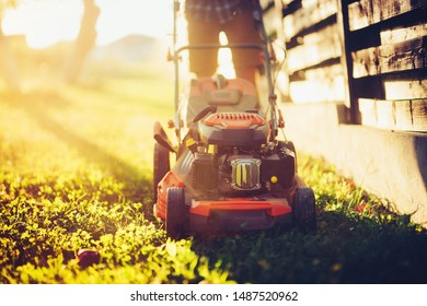 Details of landscaping and gardening. Worker using industrial lawnmower