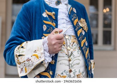 The details of man dressed in a baroque costume. A hand holding a pipe, golden buttons, vest and decorative hems. - Shutterstock ID 1963631656