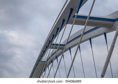 Details of a modern bridge construction Apollo bridge in Bratislava, Slovakia, uniting banks of river Danube. Details of the construction. Intense clouds on the sky.