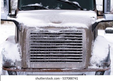 Details of modern large brown truck. Winter truck covered with ice and snow
