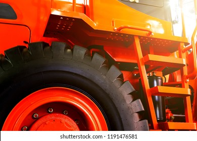Details of modern red tractor close up, bottom view, black tires