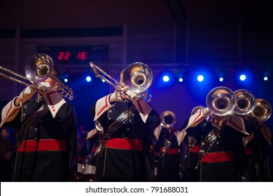 Details from a music, show and marching band. Playing musicians wind instruments in uniforms. Baritone, Mellofoon., trumpet, percussion. Concert band or windband performing during event