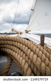 Details of an old sailing boat / schooner with white sail, wood, steel and ropes