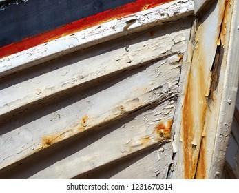 Details of an old vintage broken rusty wooden boat on land