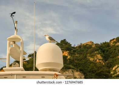 Details of the radar equipment of a boat moored in the port of Alassio with the medieval Church of the Holy Cross in the background, Alassio, Liguria, Italy