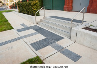 Details of railing and stairs of a modern building. Sidewalk guides for blind.