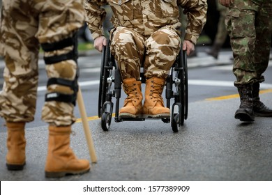 Details with a Romanian army veteran soldier, injured and disabled, sitting in a wheelchair dressed in his military desert camouflage uniform.