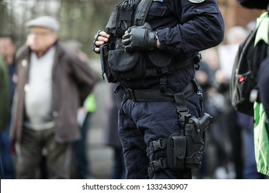 Details of the security kit of a riot police officer (including handcuffs, 9mm handgun, radio station and baton) sitting amongst civilians