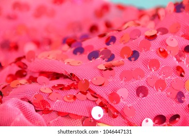 Details of sequin disks sewn on pink fabric, focus on front and fading out to the back