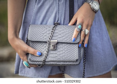 Details shoot of woman holding a leather bag