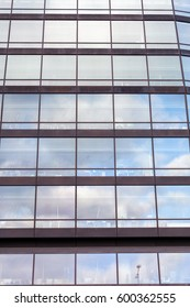 Details of a sky rise with a facade built with only windows,reflecting the sky.