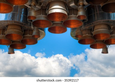 details of space rocket engine against blue sky with clouds