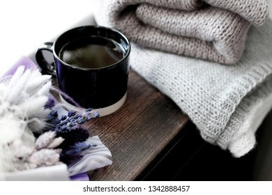 Details of still life in the home interior living room. Beautiful Cup of coffee with  bouquet of dried flowers with lavender and sweaters. Cosy autumn-winter concept