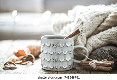 Details of still life in the home interior living room. Beautiful Cup of tea with tangerines and sweaters on wooden background . Cosy autumn-winter concept