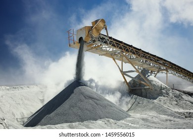 Details of stone crushing equipment at the mining factory in a cloud of dust against the blue sky, close-up. Quarry mining machinery.