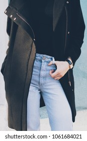 Details of stylish winter, spring or autumn outfit. Cropped photo of slender young woman wearing black coat, blue high waist jeans and gold wrist watches. Fashionable girl posing at sunny day outside.