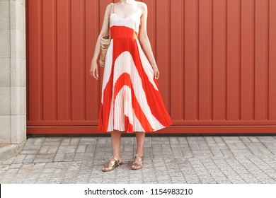 Details of stylish woman's summer outfit. Red and white midi silk dress, wicker straw bag and gold flat sandals on red street background. Trendy casual outfit. Street fashion. No face. Women's legs.