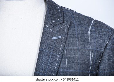 Details of a tailored suit jacket with markings on it for stitching, cutting and tailoring