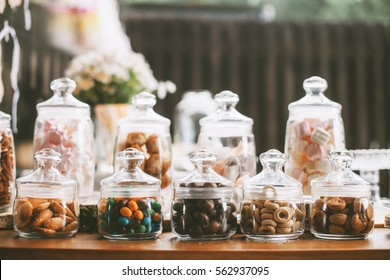 Details of a tasty candy bar with jugs of sweets, cookies and marshmallows