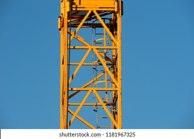 Details of a tower crane against the background of clear blue sky. Contrast of yellow paint and blue air. Metal frames and ropes. Construction or building concept. Free space to add text