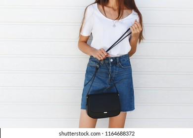 Details of trendy casual summer or spring outfit. Woman wearing blue denim mini skirt, white tshirt, small black cross body bag standing near white roller door. Everyday look. Street fashion. No face.