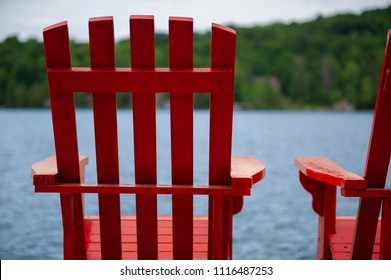 Details of two Muskoka chairs facing a calm lake.