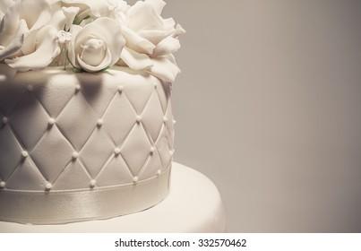 Details of a wedding cake, decoration with white fondant on grey background.