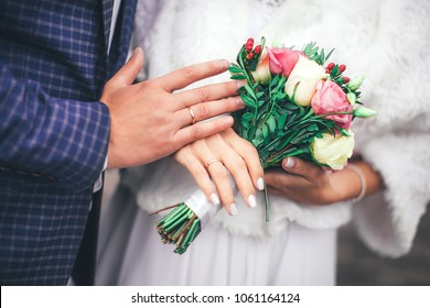 details of the wedding, the hands of the bride and groom with a ring and a beautiful tender bouquet, happy newlyweds