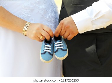 Details of a wedding photo,with pregnant bride and groom holding baby shoes in their hands.