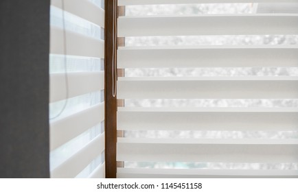 Details of white fabric roller blinds on the plastic window with wood texture in the living room.
