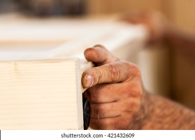 details of woodworker hands with wooden board