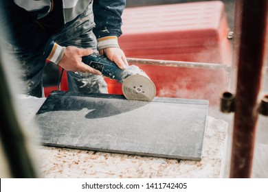 Details of worker cutting stone marble with angle grinder at construction site